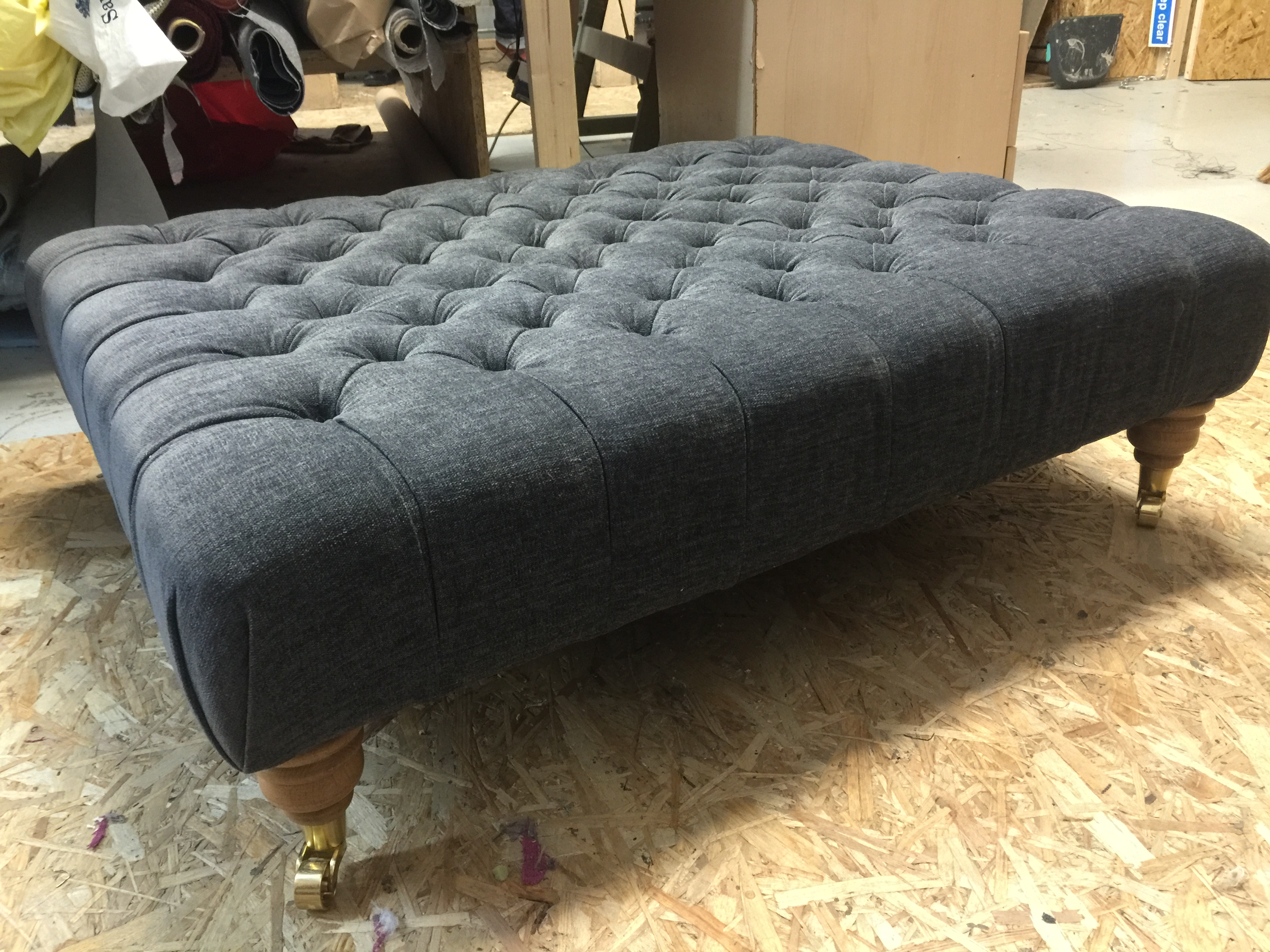 Extra large deep buttoned footstool on castor legs